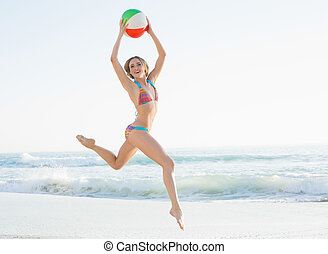 Gorgeous young woman jumping on beach holding a beach ball...
