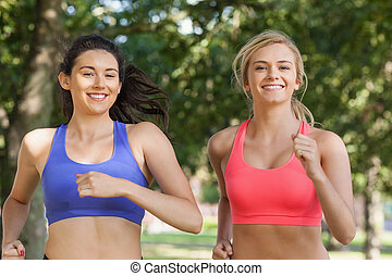 Two beautiful sporty women jogging in a park smiling at...