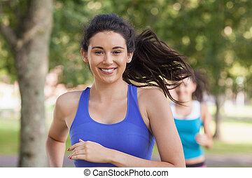 Lovely brunette woman running in a park