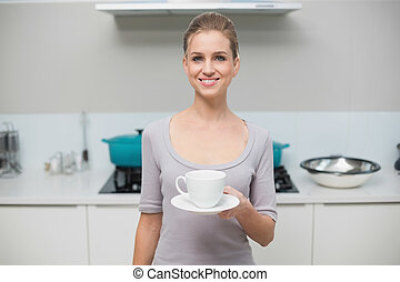 Lucky gorgeous model looking at camera holding mug standing...