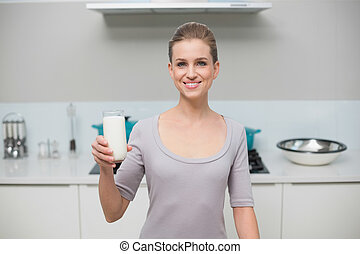 Smiling gorgeous model looking at camera holding glass of milk