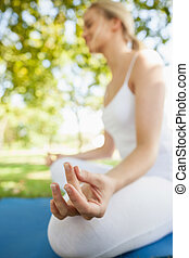 Peaceful young woman sitting on an exercise map meditating...