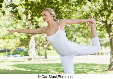 Calm young woman doing yoga standing in a park spreading her...