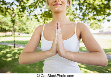 Mid section of content calm woman meditating in a park in...