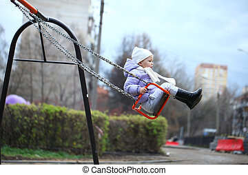 little girl riding on a swing in the park