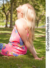 Profile view of cute young woman enjoying the sun relaxing...