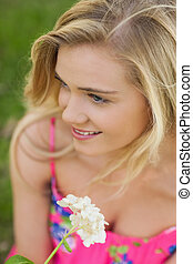 High angle view of content young woman holding a white flower