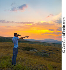 Young man in the mountains at sunset