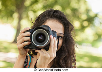 Pretty brunette woman taking a picture in a park