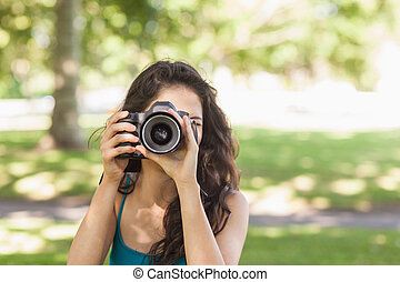 Front view of cute brunette woman taking a picture with her camera in a park