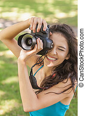 High angle view of cheerful young woman taking a picture in...