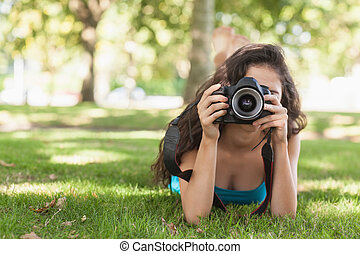Front view of brunette woman lying on a lawn for taking a picture using her camera