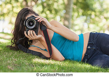 Front view of pretty brunette woman lying on a lawn taking a picture with her camera