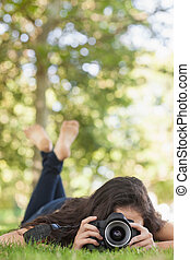 Front view of young woman lying on a lawn taking a picture