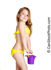 little blonde happy girl in yellow swimsuit holding toy...