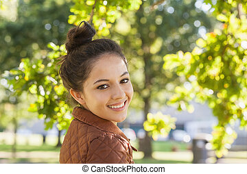 Cute brunette woman wearing a brown coat posing in a park