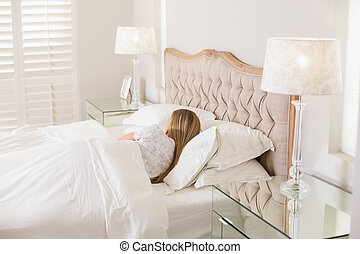Natural woman sleeping in bed in bright bedroom