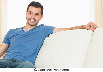 Casual happy man relaxing on couch in bright living room