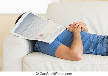 Casual man lying on couch with newspaper covering head in...