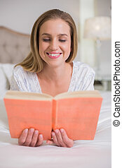 Natural smiling woman lying on bed reading in bright bedroom