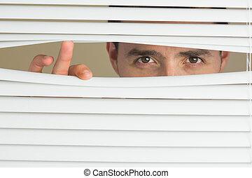 Focused male eyes spying through roller blind - Focused...