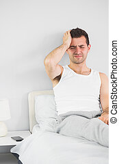 Grimacing handsome man having a headache in bright bedroom