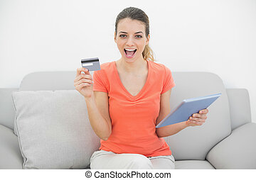Cheering brunette woman showing her credit card holding her...