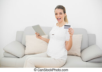 Cheering pregnant woman showing her tablet and credit card...