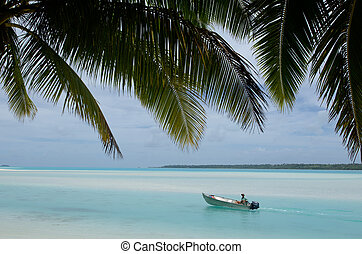 Fisherman in fishing boat on Aitutaki Lagoon Cook Islands -...