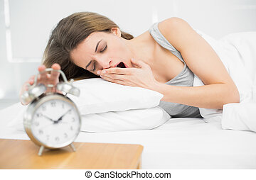 Tired brunette woman turning off the alarm clock while...
