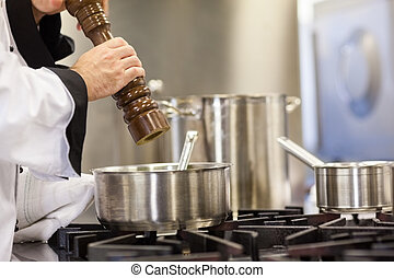 Head chef flavoring food with pepper in professional kitchen