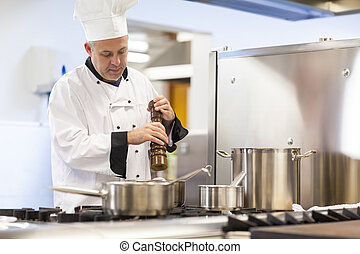 Focused head chef flavoring food with pepper in professional...