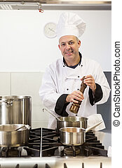 Smiling head chef using pepper mill in professional kitchen
