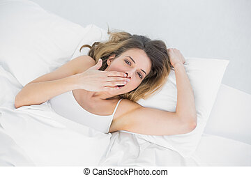Gorgeous tired woman yawning lying