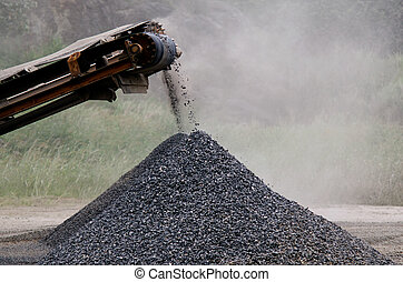 Gravel machine pouring gravel stones into a pile