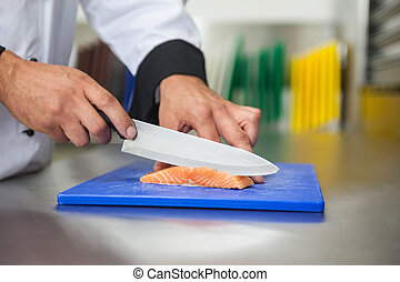 Chef slicing raw salmon with knife on blue cutting board in...