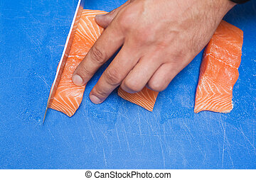 Close up of hand slicing raw salmon with sharp knife on blue...