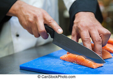 Close up of chef slicing salmon with sharp knife in...