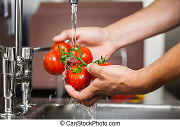 Kitchen porter washing tomatoes in professional kitchen