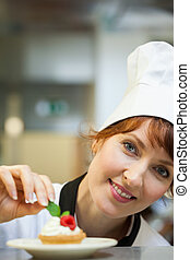 Smiling head chef putting mint leaf on little cake in...