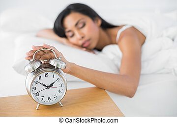 Attractive tired woman sleeping lying in her bed turning off...