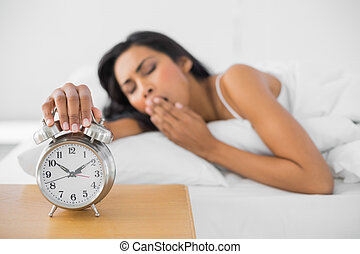 Lovely yawning woman turning off the retro alarm clock lying...