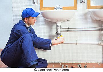 Attractive concentrating plumber repairing sink in public...