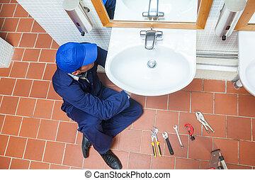 Plumber with cap repairing sink