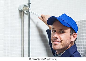 Cheerful plumber repairing shower head in public bathroom