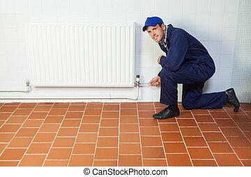 Handyman in blue boiler suit repairing a radiator smiling at camera in bright room