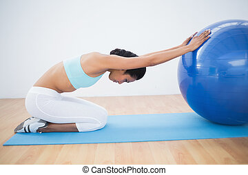 Fit woman stretching her body using a fitness ball sitting...