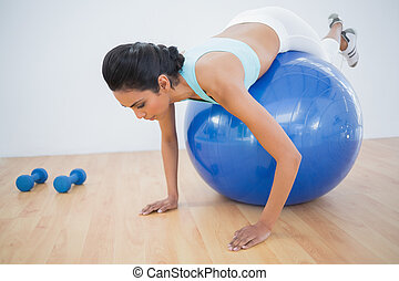 Cute sporty woman training on fitness ball in fitness hall
