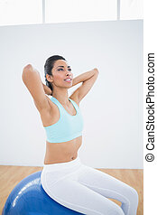 Beautiful woman stretching sitting on fitness ball in...