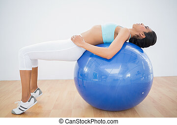 Concentrated toned woman training on fitness ball in fitness...